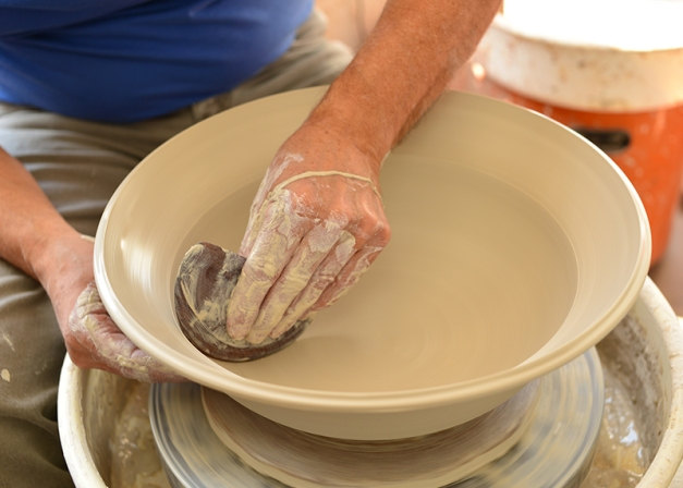 The performance continues. The master skillfully asserts pressure to the bowl's upper third moving the clay rim into position. A simple kitchen scraper provides the perfect shape for a smooth transition from concave to convex.