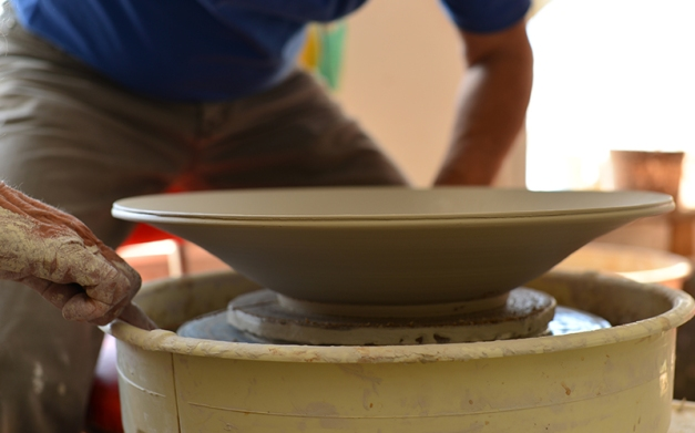 His hands part, the right reaches for a switch to cut electricity to the wheel. Each hand wraps around large metal washers connected by thin cutting wire. One smooth movement separates the foot of the bowl from the bat.