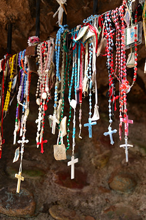 Rosaries are suspended above the shrine. Each small tag contains names and dedications.