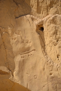 Petroglyphs carved into the soft sandstone wall.