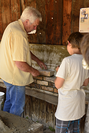 A hands on demonstration station was a popular place for young and old alike. Children were lined up to give brick laying a try under the tutelage of a very patient teacher.