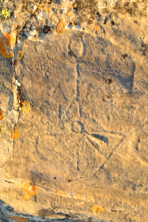 This glyph has puzzled visitors, guides and archeologists alike. The triangle shape is believed to depict a tipi, the circular shape marks the fire circle or hearth in the center of the dwelling. The simple figure placed directly above the hearth has an outstretched hand holding a bow and arrow. Why was this hunter placed above the the tipi? Was he the protector and provider of the the family? What other significance could this combination of glyphs communicate? Or was the figure carved by someone not connected to the tipi?