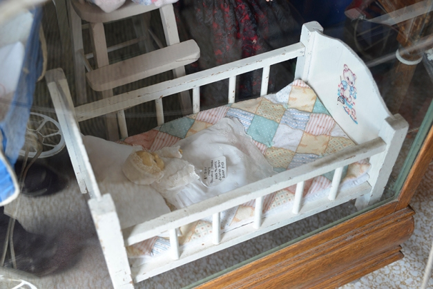 A doll cradle with minature quilt -
