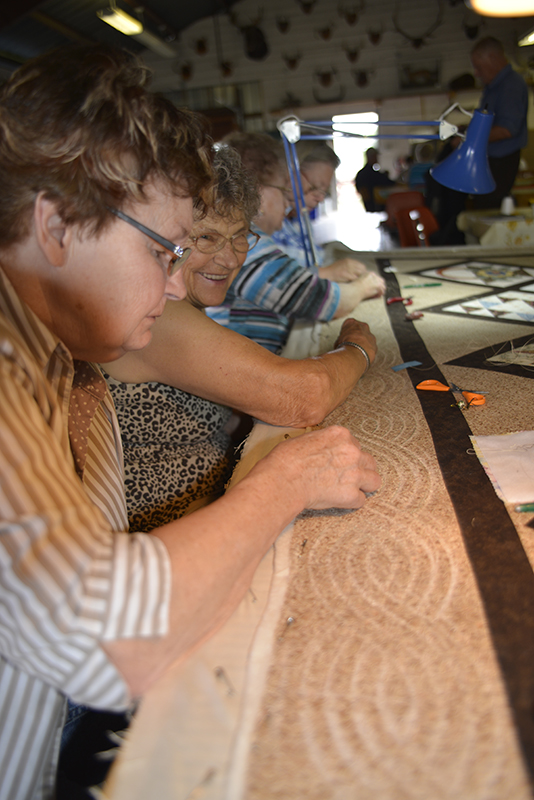 Busy quilters stitching in unison