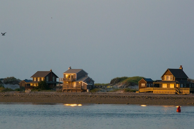 The golden light of the setting sun reflected in the windows of the cottages lining the beach on Plymouth Peninsula.