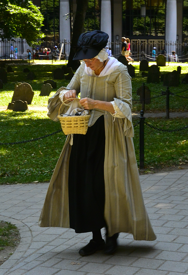 A tour guide in period costume led a group of tourists into the Granary Burial Grounds, a celebrity cemetery so to speak.