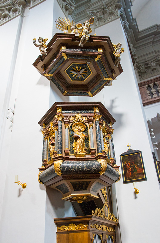 A richly decorated pulpit, no longer used these days, continues to be perched above the confessional.
